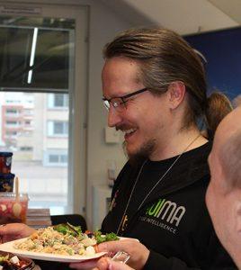 hymyilevä mies ottaa salaattia